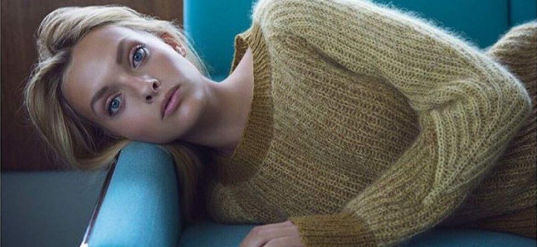 Dame som ligger på en blå sofa
