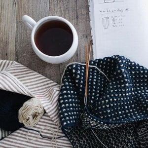 Strikkeutstyr og en kopp kaffe
